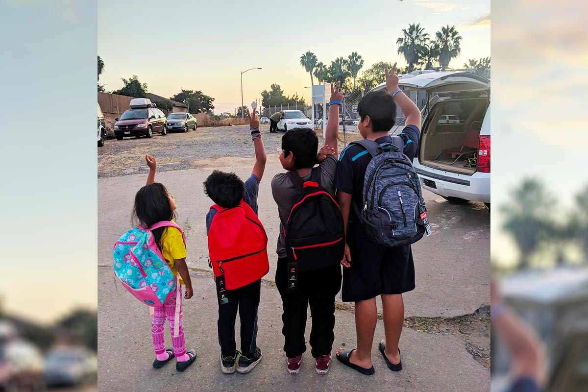 Kids in safe parking lot in San Diego with backpacks